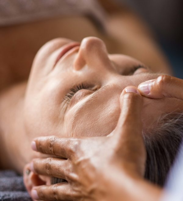 Closeup face of mature woman having facial massage at spa. Senior woman lying with closed eyes at spa while a massage therapist doing anti-aging treatment. Masseur doing head massage at wellness center.